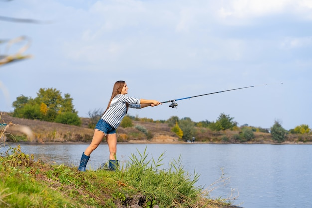 Linda garota peixes no lago.