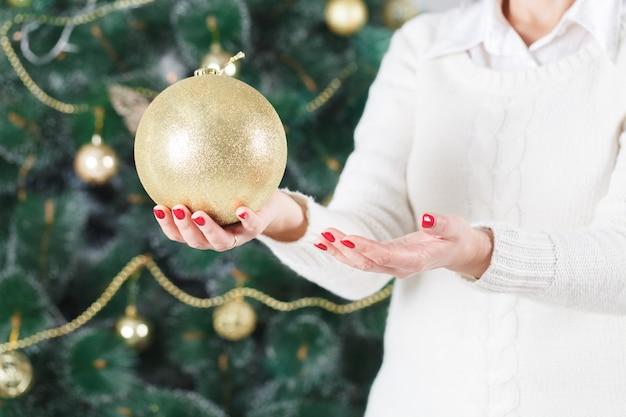 Linda garota pendura um brinquedo de natal na árvore de natal. boas festas!