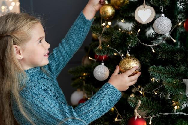 Linda garota pendurando enfeites na árvore de natal