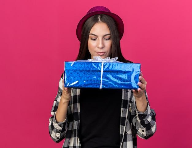 Linda garota pensando com chapéu de festa segurando e olhando para uma caixa de presente