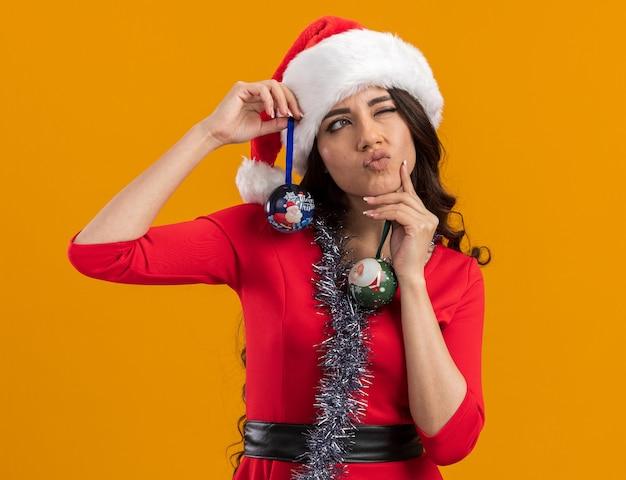 Linda garota pensativa com chapéu de papai noel e guirlanda de ouropel no pescoço segurando enfeites de natal olhando para o lado tocando o queixo com um olho fechado isolado na parede laranja