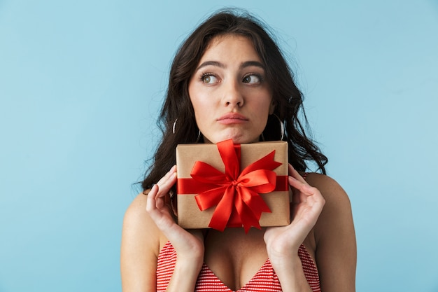 Linda garota pensativa com roupas de verão, isolada sobre o azul, segurando uma caixa de presente