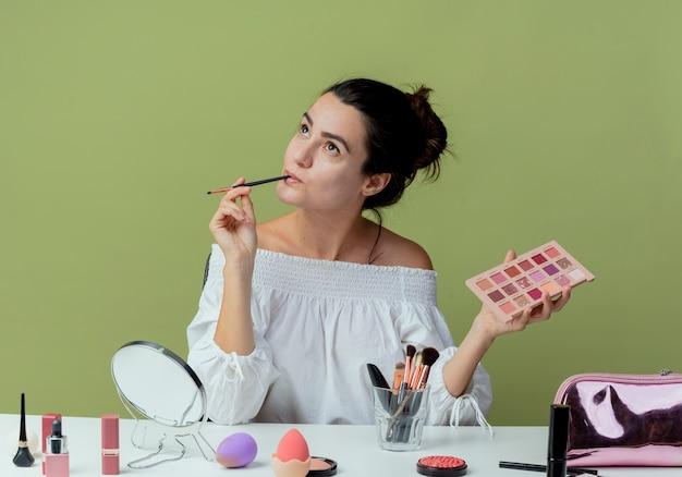 Linda garota pensativa se senta à mesa com ferramentas de maquiagem segurando uma paleta de sombras e um pincel de maquiagem olhando para cima, isolado na parede verde