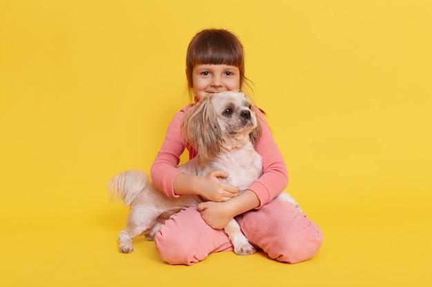 Linda garota pequena abraçando seu cachorro de estimação isolado em amarelo