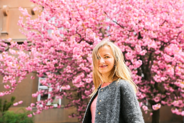 Linda garota perto das árvores sakura. mulher de vestido e casaco elegante flores cor de rosa que florescem em uzhhorod. blossom around. tempo de primavera. conceito de relaxamento e felicidade.