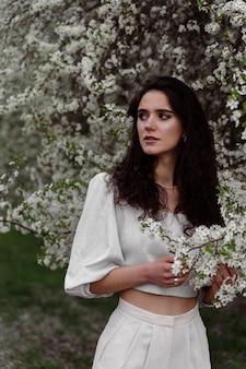 Linda garota perto de árvores florescendo no parque. caminhada ao ar livre em dia de sol. estilo de vida de uma jovem.