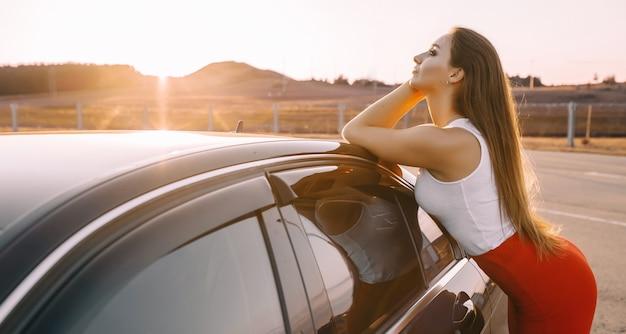 Linda garota perto de um carro à noite sob o sol do sol em um estacionamento vazio