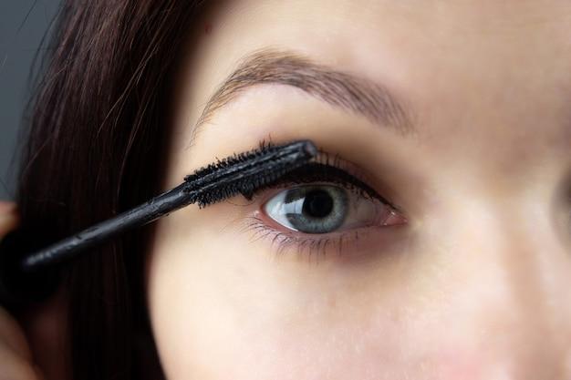Linda garota pinta os olhos com rímel close-up