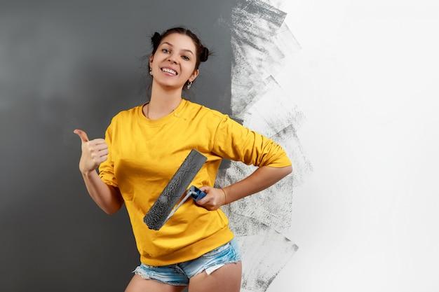 Linda garota pinta uma parede em uma jaqueta amarela com um rolo, tinta cinza. o conceito de reparação, mudança, design, interior.