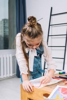 Linda garota pintando com aquarelle na folha de papel na mesa