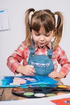 Linda garota pintando com guache azul na mesa de madeira