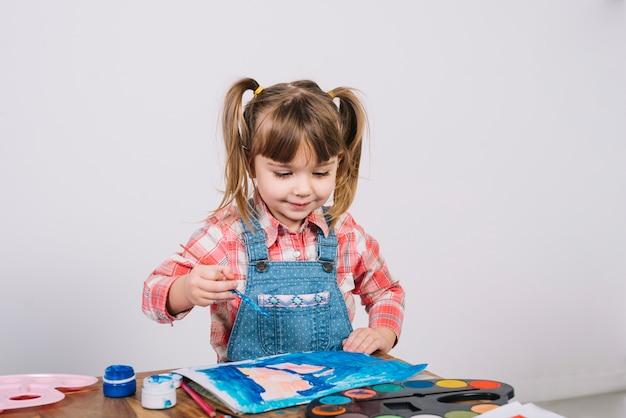 Linda garota pintando com guache na mesa de madeira