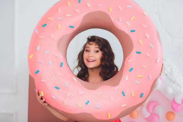 Linda garota posando com rosquinhas rosa, brincando, sobremesa, comida ruim, olha para o buraco na rosquinha, mantém rosquinhas pelos olhos