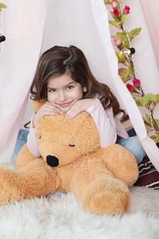 Linda garota posando com um grande urso de pelúcia