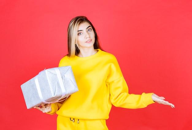 Linda garota posando com uma caixa de presente na parede vermelha