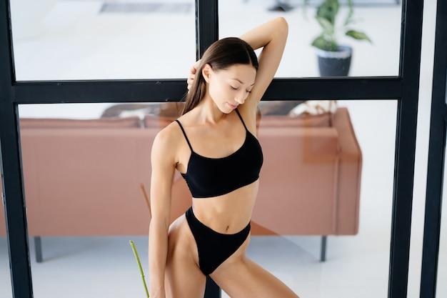 Linda garota posando de lingerie na sala de estar