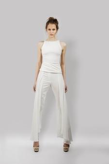 Linda garota posando em calças e blusa. retrato do comprimento total do modelo de moda.