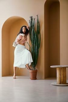 Linda garota posando em um arco decorativo com um vaso de cactos
