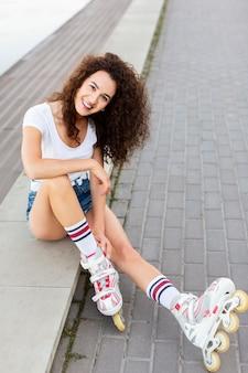 Linda garota posando enquanto está sentada e de patins