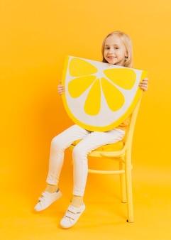 Linda garota posando enquanto segura a fatia de limão decoração