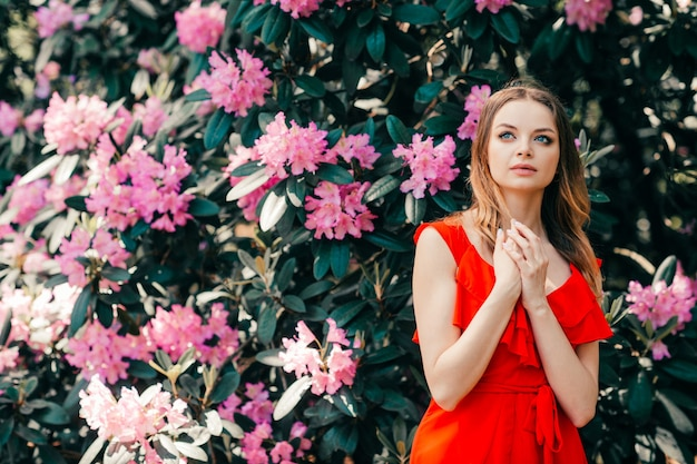 Linda garota posando entre uma árvore florida