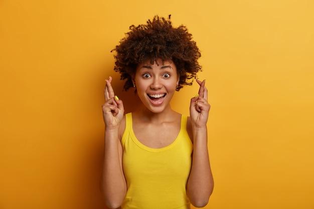 Linda garota positiva com penteado afro acredita que os sonhos se tornam realidade, mantém os dedos cruzados, espera que algo de bom aconteça, veste-se casualmente, ri e olha diretamente, posa dentro de casa
