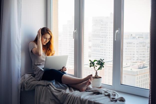 Linda garota positiva usando laptop, sentado no parapeito da janela em um apartamento da cidade. jovem mulher ruiva trabalhando em casa. conceito autônomo.