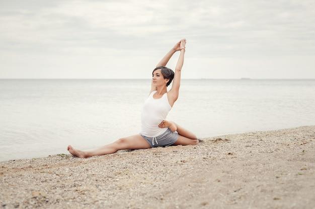 Linda garota praticando ioga na praia perto do mar.