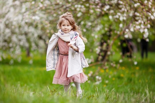 Linda garota pré-adolescente com longos cabelos loiros desfrute da flor de maçã da primavera menina pré-escolar correndo nas flores da árvore do jardim. primavera. copie o espaço