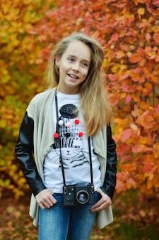 Linda garota pré-adolescente com uma fotocâmera antiga no outono