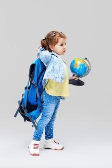 Linda garota pré-escolar com uma mochila azul nas costas, segurando um globo nas mãos