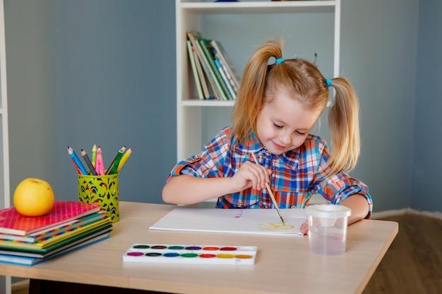 Linda garota pré-escolar pinta em casa à mesa.