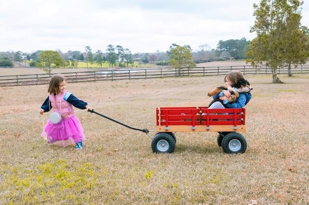 Linda garota puxando a irmã e o cachorrinho em uma carroça vermelha irmãs pequenas se divertindo no quintal