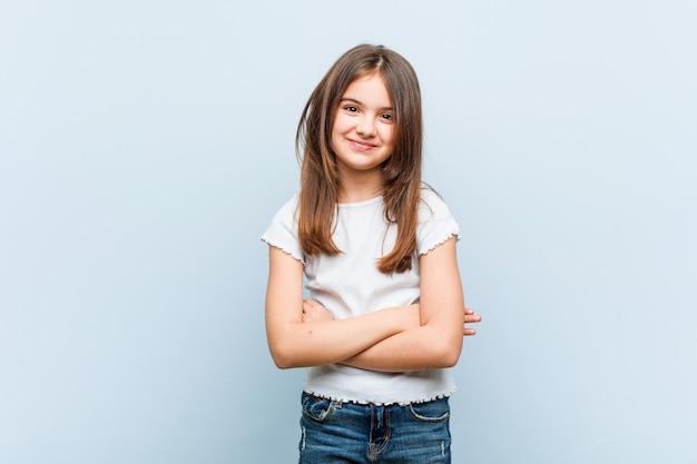 Linda garota que se sente confiante, cruzando os braços com determinação.