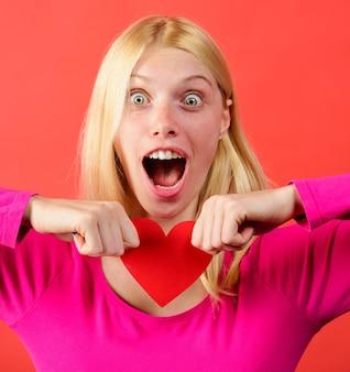 Linda garota rasgando o coração de papel vermelho. quebra de relações. problemas de relacionamento. amor não correspondido.