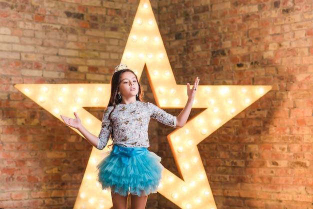 Linda garota, realizando na frente de uma estrela brilhante contra a parede de tijolos