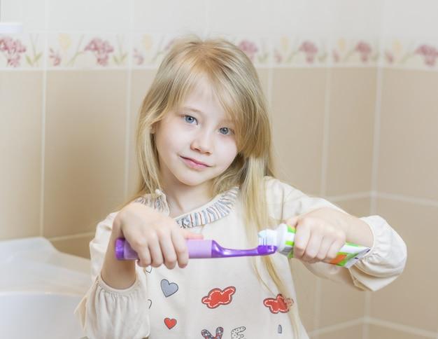Linda garota recebe creme dental em uma escova de dentes elétrica.