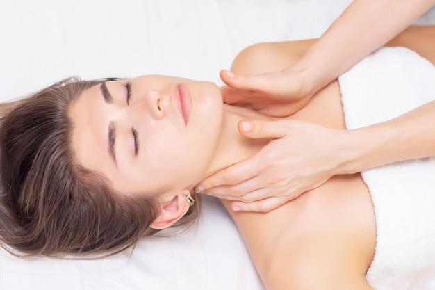 Linda garota recebe massagem em um salão de spa. conceito de massagem e saúde. reumatismo, artrose