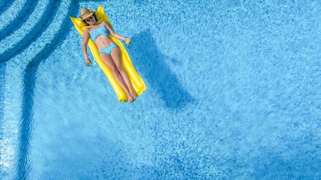 Linda garota relaxando na piscina mulher na vista aérea do colchão inflável