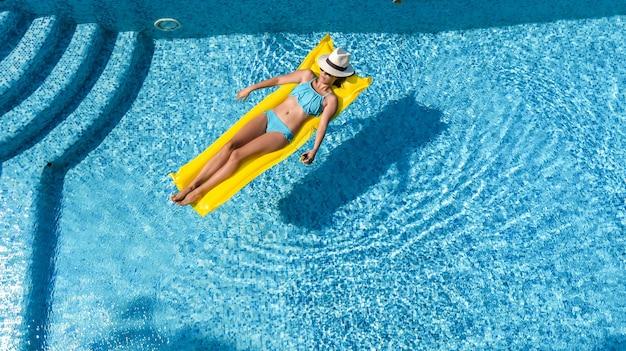Linda garota relaxando na piscina, mulher nadando em colchão inflável e se divertindo
