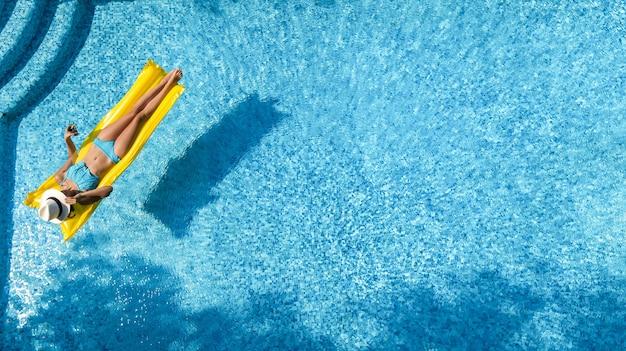 Linda garota relaxando na piscina, mulher nadando no colchão inflável e se divertindo na água nas férias em família, resort tropical de férias, vista aérea do drone de cima