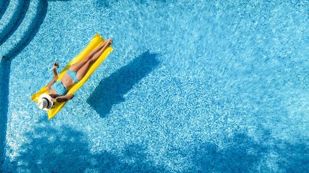 Linda garota relaxando na piscina, mulher no colchão inflável, vista aérea