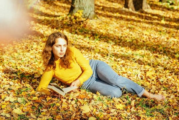 Linda garota relaxando no parque no outono com um livro