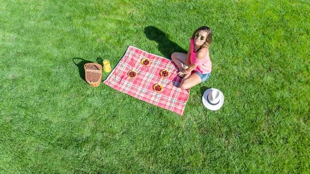 Linda garota relaxante na grama, fazendo piquenique de verão no parque ao ar livre, vista aérea zangão de cima