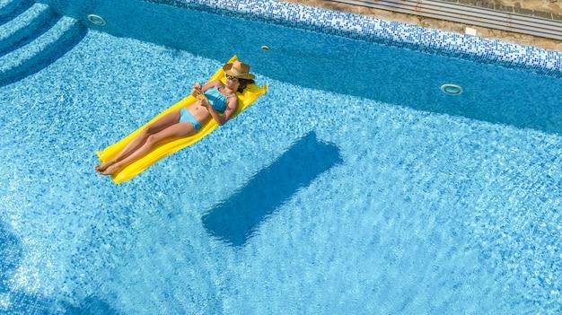 Linda garota relaxante na piscina, mulher nada no colchão inflável e se diverte na água em férias em família, estância de férias tropical, vista aérea zangão de cima