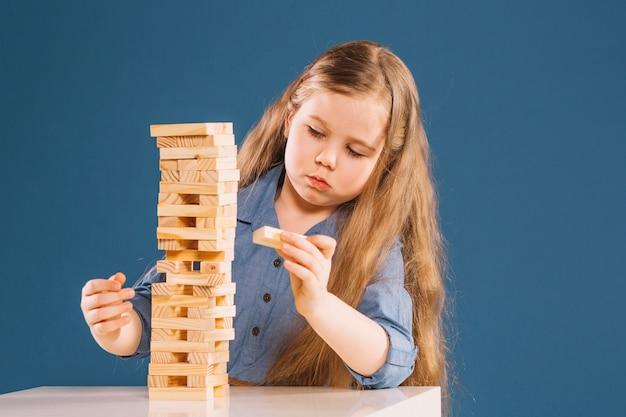 Linda garota removendo blocos da torre de jenga