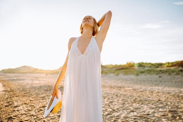 Linda garota respirando na praia com o mar ao fundo.