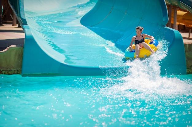 Linda garota retira os slides no parque aquático.
