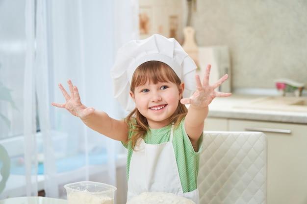 Linda garota rindo cozinha acenando as mãos