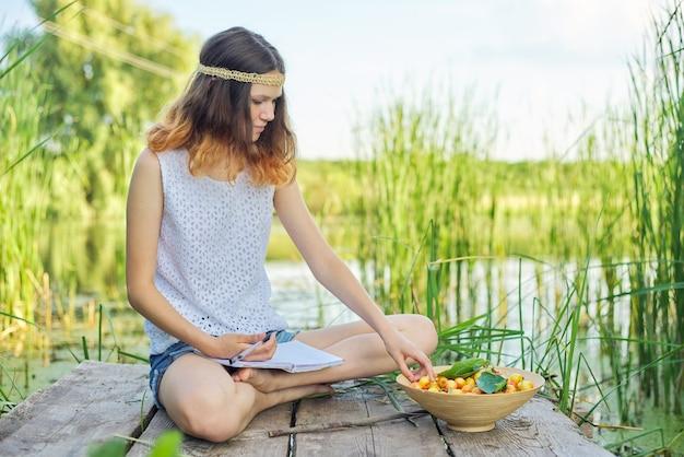 Linda garota romântica adolescente sentada na ponte perto da água, a garota escreve no caderno experiências pessoais, tigela de cerejas, apreciando a beleza da natureza pitoresca e as férias de verão, copie o espaço